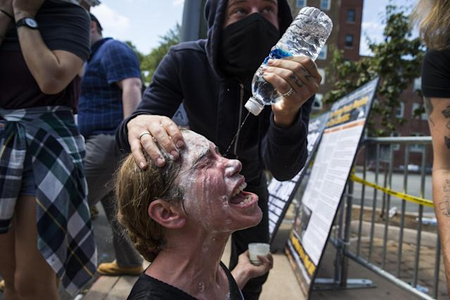 <p>A woman has a special mixture and water poured in her eyes after being hit with pepper spray during clashes with between White Supremacists and counter protestors at Emancipation Park where the White Nationalists are protesting the removal of the Robert E. Lee monument in Charlottesville, Va., on Aug. 12, 2017. (Photo: Samuel Corum/Anadolu Agency/Getty Images) </p>