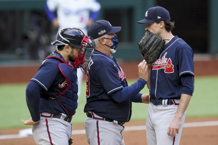 Atlanta Braves manager Brian Snitker talks with starting pitcher Max Fried during the first inning in Game 6 of a baseball National League Championship Series against the Los Angeles Dodgers Saturday, Oct. 17, 2020, in Arlington, Texas. (AP Photo/Eric Gay)