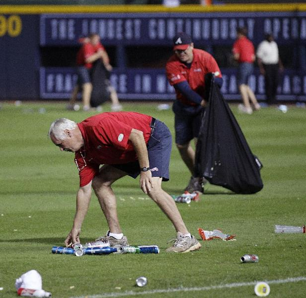 An Atlanta Braves official picks up trash on the field during the eighth inning of the National League wild card playoff baseball game against the St. Louis Cardinals, Friday, Oct. 5, 2012, in Atlanta. The Cardinals won baseball's first wild-card playoff, taking advantage of a disputed infield fly call that led to a protest and fans littering the field with debris to defeat the Braves 6-3. (AP Photo/John Bazemore)