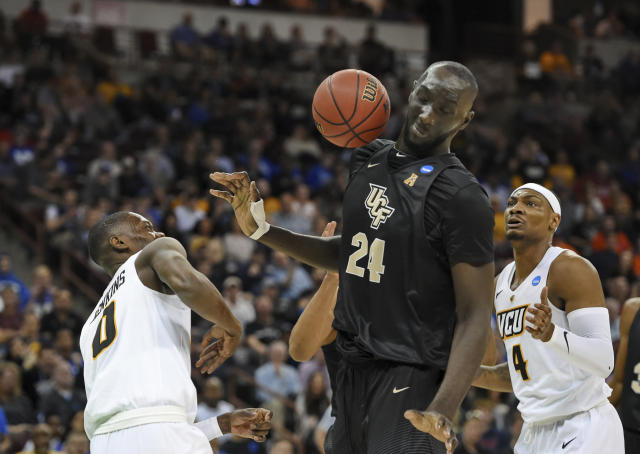 Central Florida's Tacko Fall (24) dodges a loose ball with VCU's De'Riante Jenkins and Corey Douglas (4) defending during the first half of a first-round game in the NCAA mens college basketball tournament Friday, March 22, 2019, in Columbia, S.C. (AP Photo/Richard Shiro)