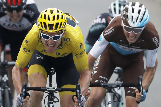 Britain's Geraint Thomas, wearing the overall leader's yellow jersey, grimaces as he sprints with France's Romain Bardet, right, and Ireland's Daniel Martin, left, towards the finish line of the nineteenth stage of the Tour de France cycling race over 200.5 kilometers (124.6 miles) with start in Lourdes and finish in Laruns, France, Friday July 27, 2018. (AP Photo/Peter Dejong)
