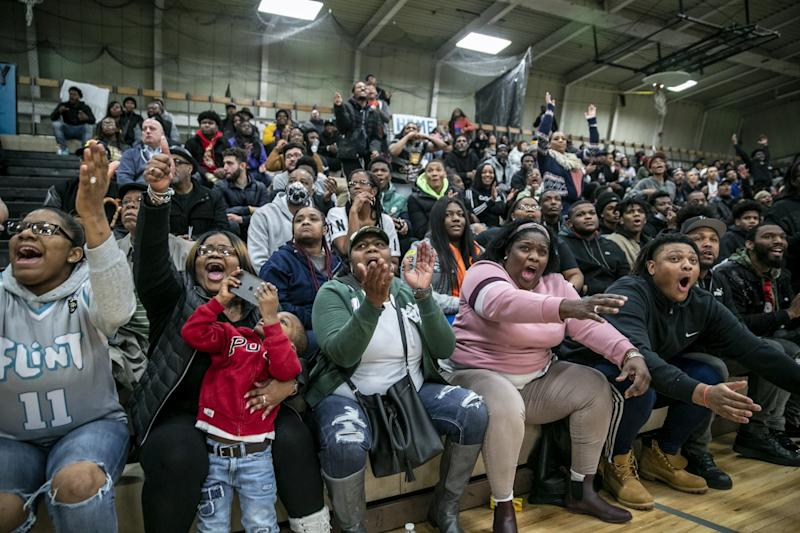Several members of Taevion Rushing's family cheer him on during a game between Flint and Beecher high schools.