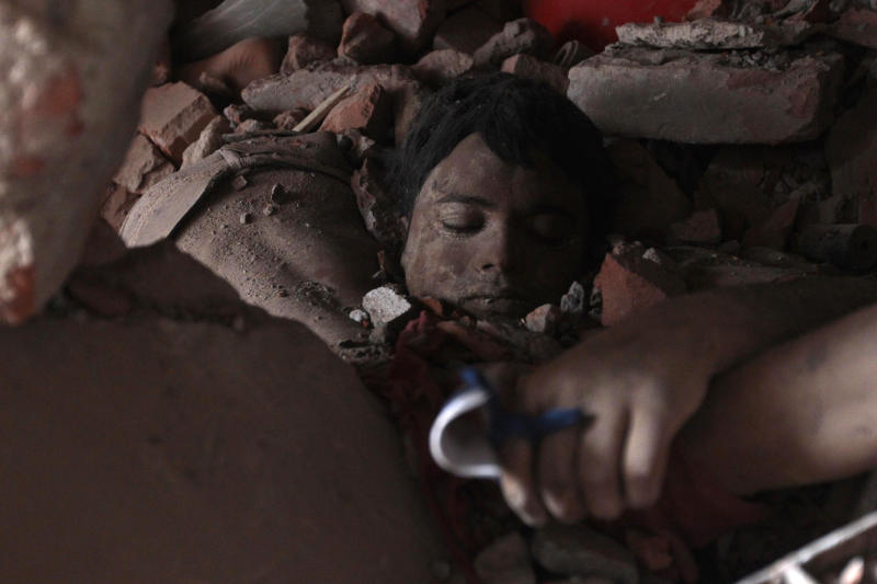 A victim's body lies amid rubble at the site of a building that collapsed Wednesday in Savar, near Dhaka, Bangladesh,Thursday, April 25, 2013. By Thursday, the death toll reached at least 194 people as rescuers continued to search for injured and missing, after a huge section of an eight-story building that housed several garment factories splintered into a pile of concrete. (AP Photo/A.M.Ahad)