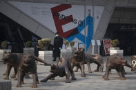 In this photo taken Tuesday, Feb. 11, 2020, a security looks past sculptures outside a quiet mall in Beijing, China. Millions of Chinese workers and entrepreneurs are bearing the rising costs of an anti-virus campaign that has shut down large sections of the economy. The government has imposed restrictions nationwide that have stalled travel and sales of real estate and autos. (AP Photo/Ng Han Guan)