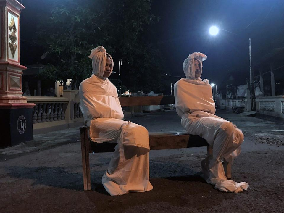 Two volunteers sit on a bench as they play the role of 'pocong', or known as 'shroud ghost', to make people stay at home amid the spread of coronavirus in Indonesia on April 1.