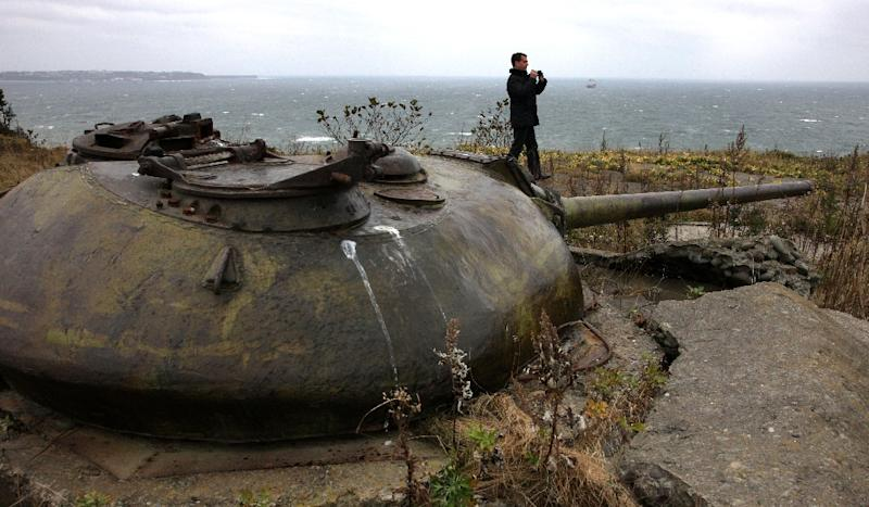 Former Russian President Dmitry Medvedev walks near a Soviet-era fortifications during his visit to one of the Kuril islands in 2010