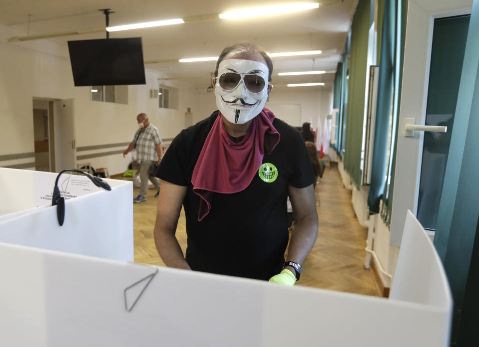 A man, wearing a face mask, prepares to cast his vote during presidential election in Warsaw, Poland, Sunday, June 28, 2020. The election will test the popularity of incumbent President Andrzej Duda who is seeking a second term and of the conservative ruling party that backs him. (AP Photo/Petr David Josek)