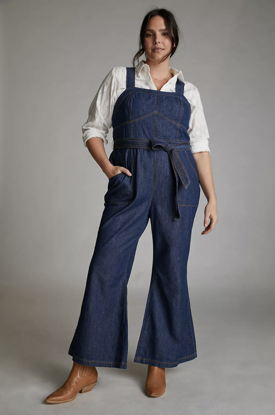 plus size brunette model posing in denim jumpsuit and white shirt and brown boots