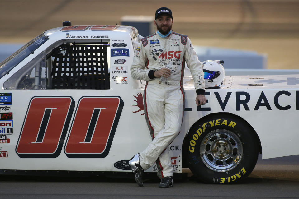 Josh Reaume stands with his race vehicle prior to the NASCAR Truck Series auto race at Phoenix Raceway, Friday, Nov. 6, 2020, in Avondale, Ariz. (AP Photo/Ralph Freso)