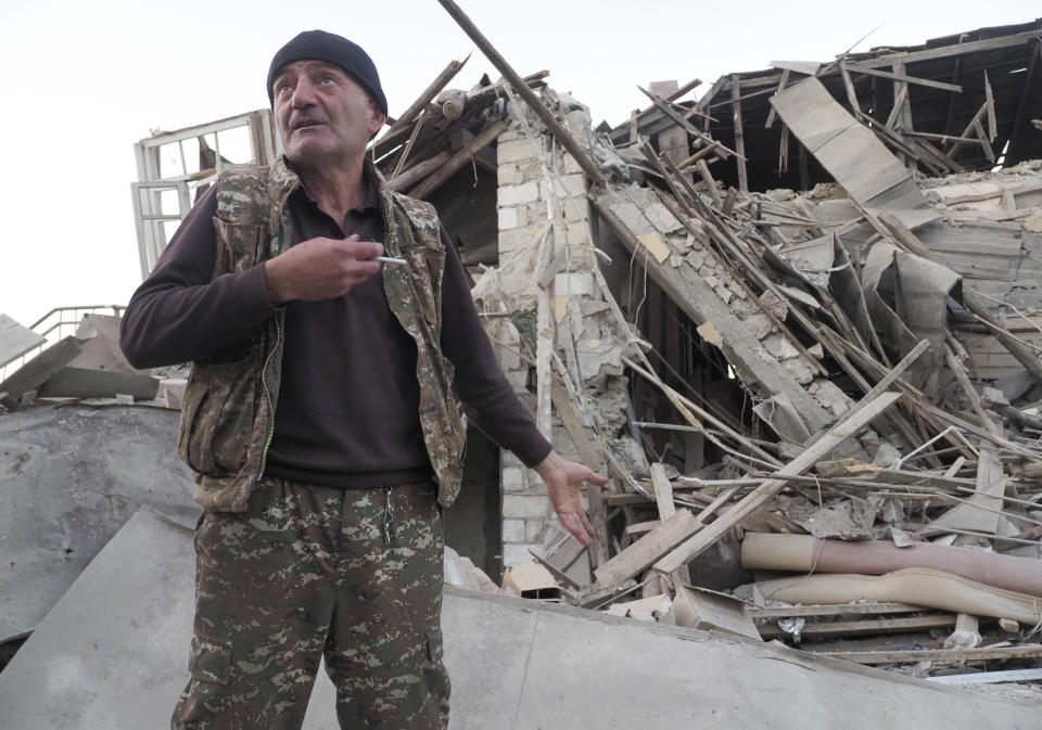 A man stands near his neighbour's house destroyed by shelling by Azerbaijan's artillery during a military conflict in Stepanakert, the separatist region of Nagorno-Karabakh, Saturday, Oct. 17, 2020. The latest outburst of fighting between Azerbaijani and Armenian forces began Sept. 27 and marked the biggest escalation of the decades-old conflict over Nagorno-Karabakh. The region lies in Azerbaijan but has been under control of ethnic Armenian forces backed by Armenia since the end of a separatist war in 1994. (AP Photo)