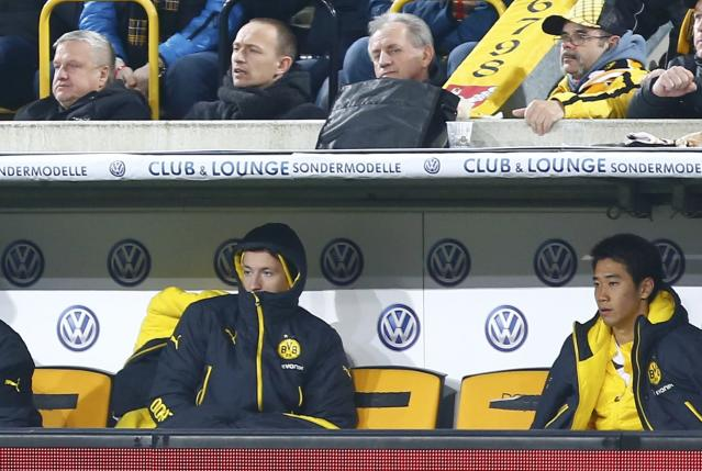 Borussia Dortmund's Marco Reus (L) and Japan's midfielder Shinji Kagawa sit on the bench during their German Cup (DFB Pokal) soccer match against Dynamo Dresden in Dresden March 3, 2015. REUTERS/Hannibal Hanschke (GERMANY - Tags: SOCCER SPORT) DFB RULES PROHIBIT USE IN MMS SERVICES VIA HANDHELD DEVICES UNTIL TWO HOURS AFTER A MATCH AND ANY USAGE ON INTERNET OR ONLINE MEDIA SIMULATING VIDEO FOOTAGE DURING THE MATCH.
