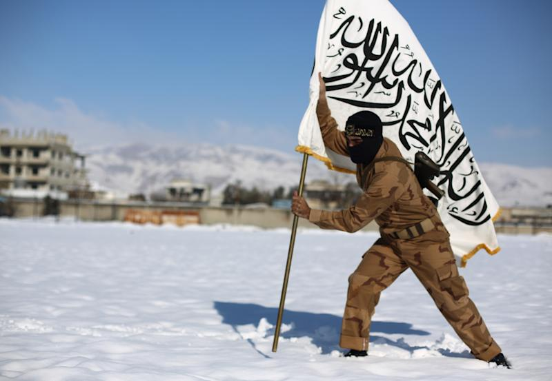 A rebel fighter with the Jaysh al-Islam (Army of Islam) places their flag in the snow in Eastern al-Ghouta, a rebel-held region outside Damascus, Syria, on January 11, 2015