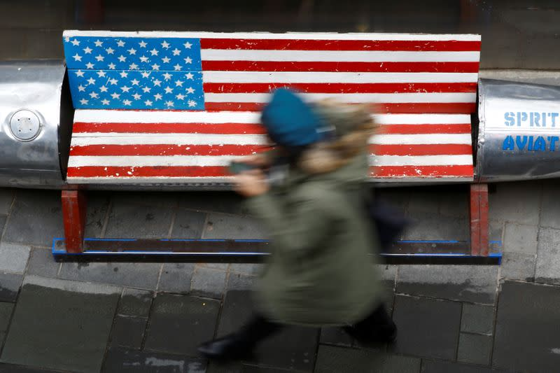 FILE PHOTO: Woman walks past a bench painted in the colours of the U.S. flag outside a clothing store in Beijing