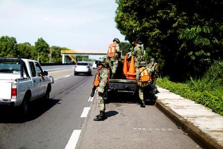 Military police officers remove a checkpoint from a road in Tuxtla Chico