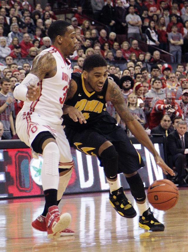 Iowa's Roy Devyn Marble, right, drives the lane against Ohio State's Lenzelle Smith during the first half of an NCAA college basketball game Sunday, Jan. 12, 2014, in Columbus, Ohio. (AP Photo/Jay LaPrete)