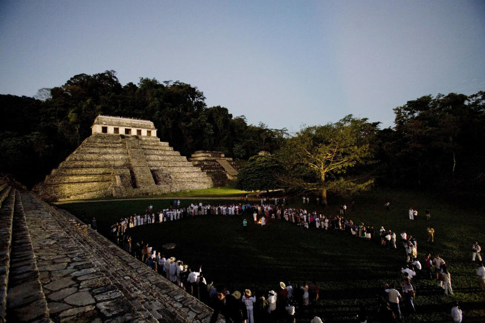 FILE - In this March 10, 2008 file photo, participants of 'Indigenous People to Heal Our Mother Earth'' hold a pre-dawn ceremony at the foot of Mayan ruins in Palenque, Mexico. Mexico's president-elect Andres Manuel Lopez Obrador wants to build a train that would run from Cancun to Palenque, but it's not the first time ambitious rail projects have been proposed: current President Enrique Pena Nieto announced in 2012 he would build a rapid train link connecting the Riviera Maya with Merida. It was cancelled due to a lack of funds. (AP Photo/Alexandre Meneghini, File)
