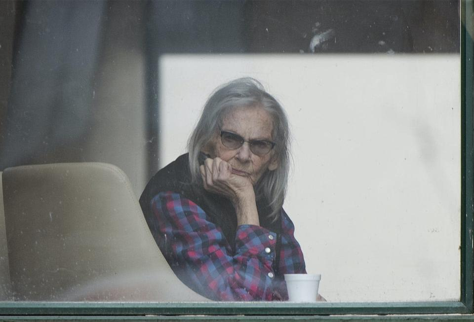 An elderly woman with long grey hair peers out the window of a long-term care home.