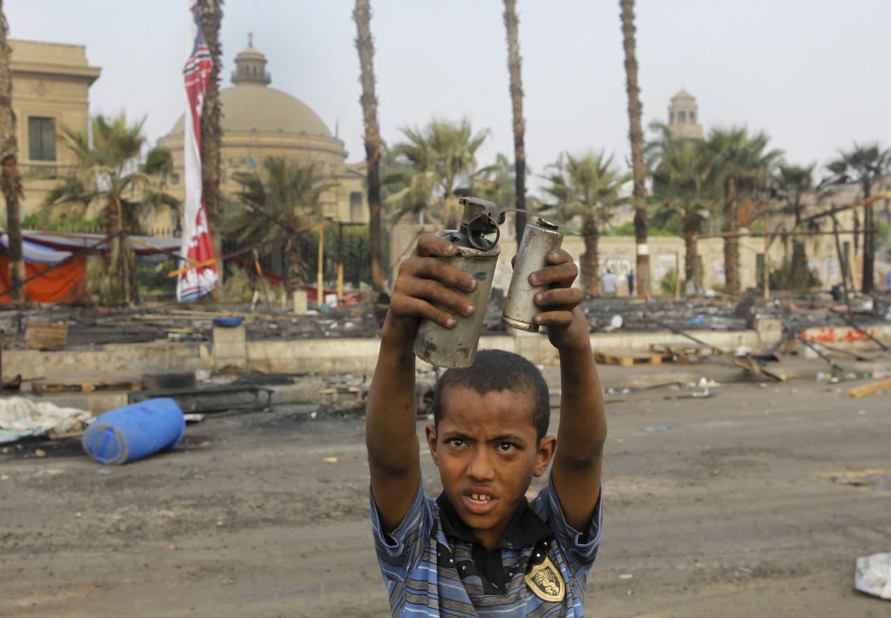 An Egyptian child displays empty tear gas canisters among the debris of a protest camp in Nahda Square, near Cairo University in Giza, Cairo, Egypt, Thursday, Aug. 15, 2013. Egypt faced a new phase of uncertainty on Thursday after the bloodiest day since its Arab Spring began, with over 300 people reported killed and thousands injured as police smashed two protest camps of supporters of the deposed Islamist president. Wednesday's raids touched off day-long street violence that prompted the military-backed interim leaders to impose a state of emergency and curfew, and drew widespread condemnation from the Muslim world and the West, including the United States. (AP Photo/Amr Nabil)