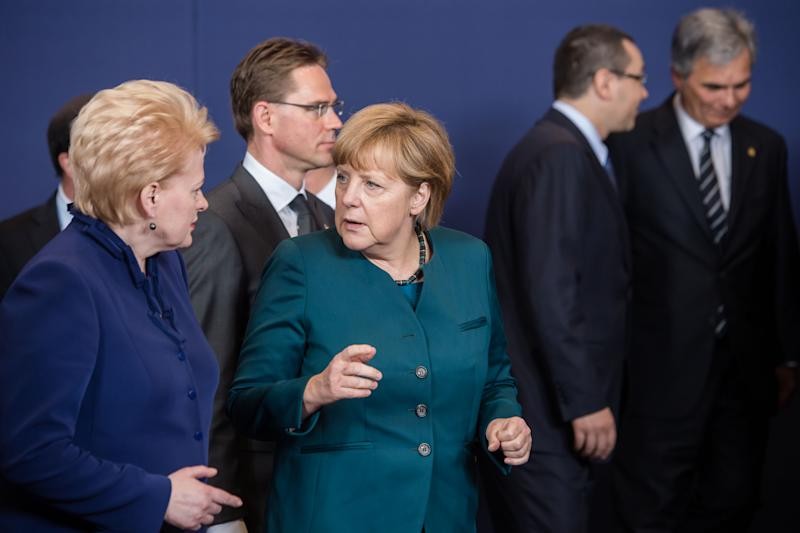 German Chancellor Angela Merkel, center, talks with Lithuania's President Dalia Grybauskaite, left, as they walk away after a group photo was taken during an EU summit in Brussels on Wednesday, May 22, 2013. Leaders from the 27 European Union countries gather in Brussels for one of their regular European Council sessions. On the agenda is the increasingly controversial subject of tax evasion. Countries such as Austria and Luxembourg which have lucrative, and somewhat opaque, banking systems have begun to fight back against efforts to improve the transparency of the EU's financial system.(AP Photo/Geert Vanden Wijngaert)