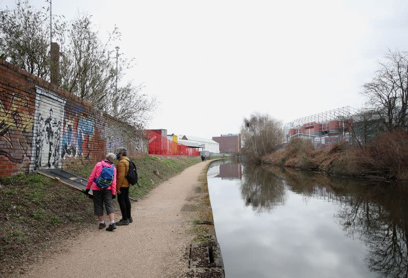 People look at a mural of England soccer player Marcus Rashford kicking down the door of number 10 Downing Street next to Manchester Canal in Manchester