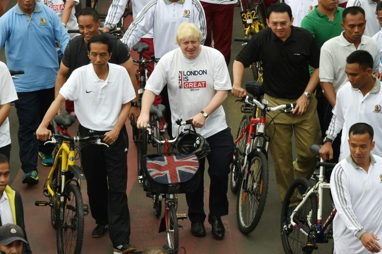 Boris Johnson, seen in his mayor of London days on a visit to Jakarta, says the coronavirus is a 'wake-up call' to the risks of being overweight and junk food advert bans and more biking can help tackle the issue
