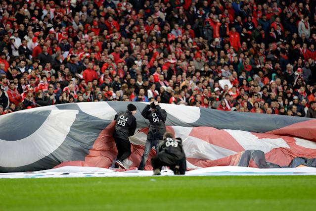 Workers holding an advertising banner struggle with the wind before the start of the Portuguese league soccer match between Benfica and Sporting Sunday, Feb. 9 2014, at Benfica's Luz stadium in Lisbon. Strong winds damaged the stadium roof before kick off and debris fell on the pitch and stands. It was decided the match should be postponed for safety reasons. (AP Photo/Armando Franca)