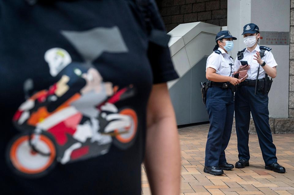 A person (L), wearing a shirt in support of convicted Tong Ying-kit, stands outside the High Court in Hong Kong, China, 27 July 2021.Tong Ying-kit, 24, is the first defendant to be found guilty for secession and terrorism under the Beijing-imposed national security law  (EPA)