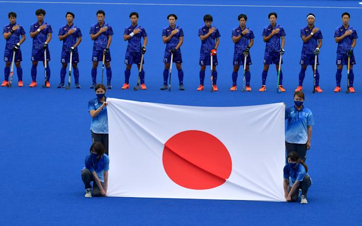 <p>Players of Japan listen to their national anthem before their men's pool A match of the Tokyo 2020 Olympic Games field hockey competition against New Zealand, at the Oi Hockey Stadium in Tokyo on July 27, 2021. (Photo by Luis Acosta / AFP)</p>