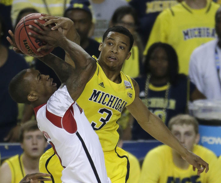 Michigan guard Trey Burke (3) works against Louisville guard Russ Smith (2) during the first half of the NCAA Final Four tournament college basketball championship game Monday, April 8, 2013, in Atlanta. (AP Photo/Chris O'Meara)