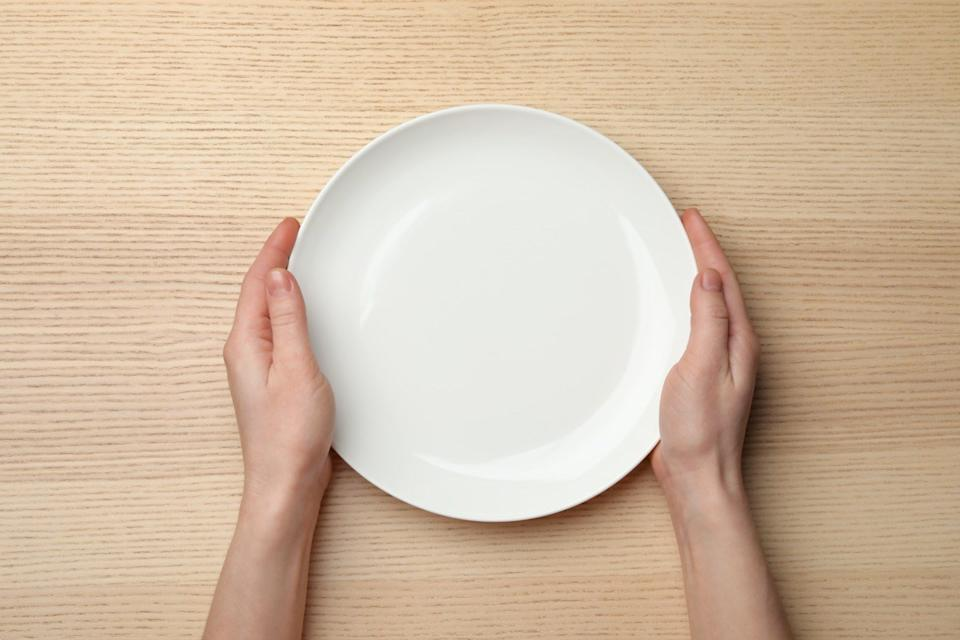 Woman with empty plate at wooden table, top view
