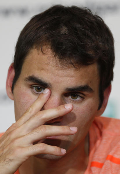 Switzerland's Roger Federer answers reporters during a press conference after losing to France's Jo-Wilfried Tsinga in their quarterfinal match of the French Open tennis tournament at the Roland Garros stadium Tuesday, June 4, 2013 in Paris. (AP Photo/Petr David Josek)