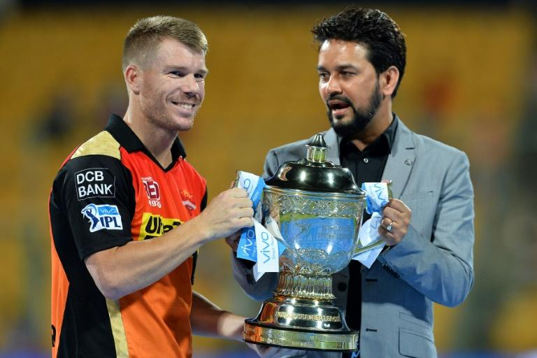 Sunrisers Hyderabad captain David Warner (L) collects the trophy from BCCI president Anurag Thakur after the team's victory against Royal Challengers Bangalore in the final Twenty20 match of the 2016 Indian Premier League (IPL), in May 2016