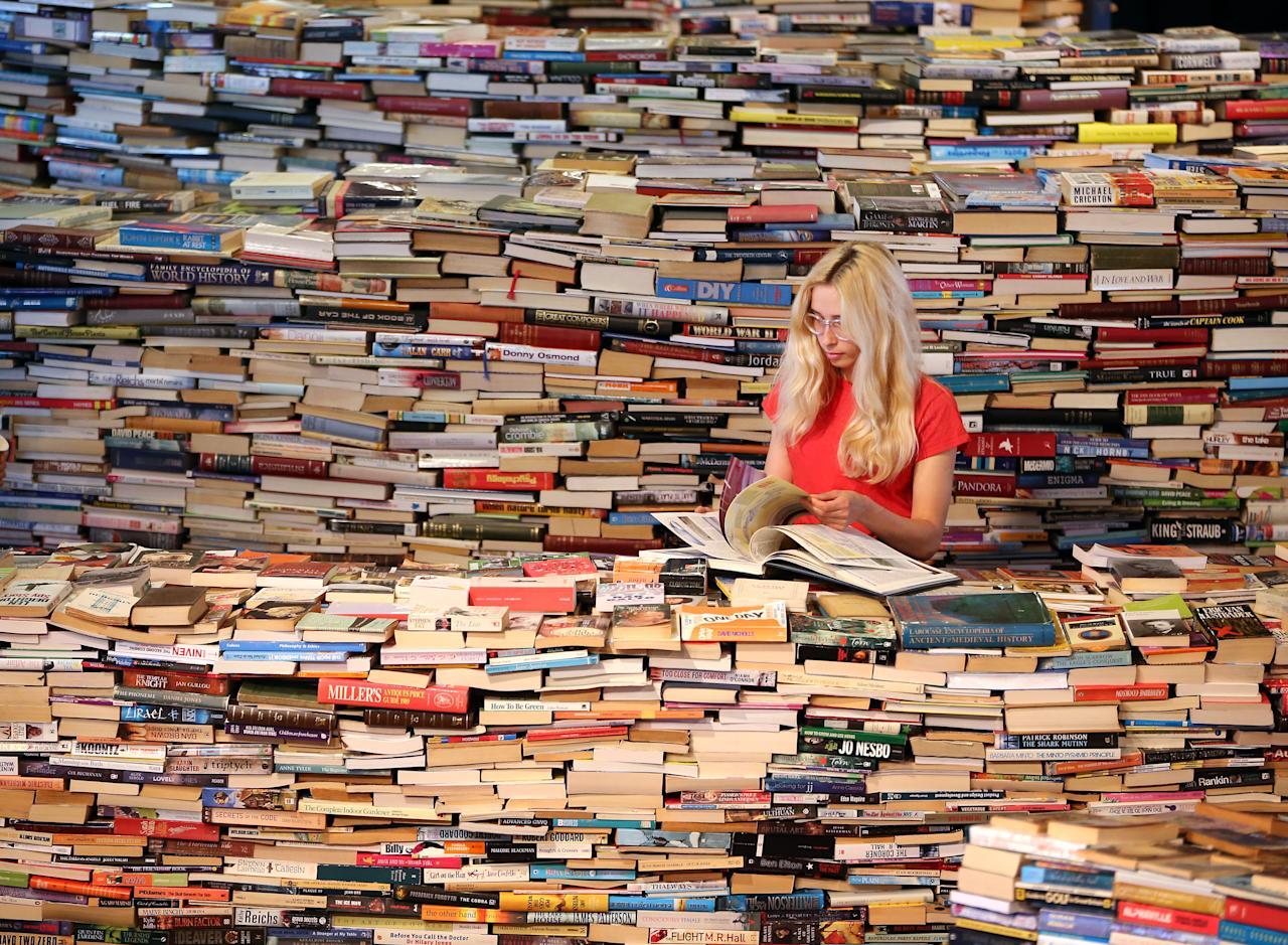 LONDON, ENGLAND - JULY 31:  Employee Tilly Shiner looks at a book in the aMAZEme labyrinth at The Southbank Centre on July 31, 2012 in London, England. Brazilian artists Marcos Saboya and Gualter Pupo used 250,000 books to create the maze which will be on display until August 25, 2012.  (Photo by Peter Macdiarmid/Getty Images)