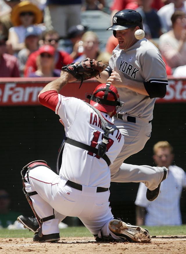 New York Yankees' Lyle Overbay, right, scores on a single by Jayson Nix past Los Angeles Angels catcher Chris Iannetta during the third inning of a baseball game in Anaheim, Calif., Sunday, June 16, 2013. (AP Photo/Chris Carlson)