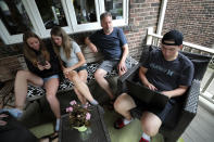 From left, twins Ruby and Lola, their father, David Wood, and their brother, Ethan, sit together on their porch in Toronto, Canada, on Monday, July 12, 2021. When Canada recently began immunizing children from 12 years of age, Amanda Wood, who manages child actors, and her architect husband didn't hesitate to get the kids vaccinated. (AP Photo/Kamran Jebreili)