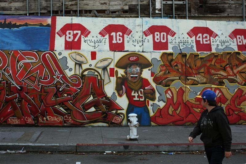 A youngster looks at a makeshift memorial to former San Francisco 49ers in Washington Square in San Francisco, California.