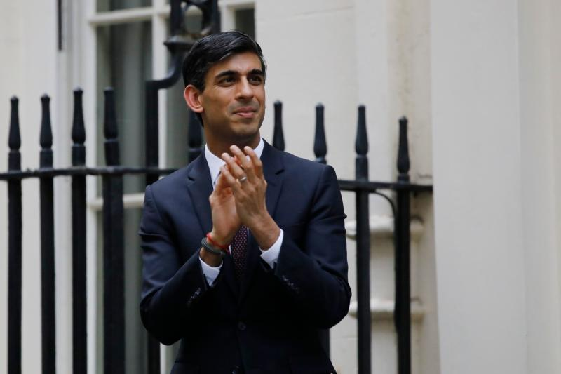 "Britain's Chancellor of the Exchequer Rishi Sunak participates in a national ""clap for carers"" to show thanks for the work of Britain's NHS (National Health Service) workers and other frontline medical staff around the country as they battle with the novel coronavirus pandemic, in Downing Street in London on May 21, 2020. - The British government on on May 21 announced that foreign care workers would be exempt from a charge imposed on migrants to fund the health service, after an outcry sparked by the coronavirus outbreak. (Photo by Tolga AKMEN / AFP) (Photo by TOLGA AKMEN/AFP via Getty Images)"