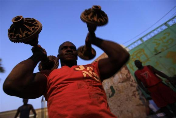 A member of the national weightlifting team lifts weights as he prepares to compete with other athletes for the selection of the Olympics team in Khartoum February 28, 2012.