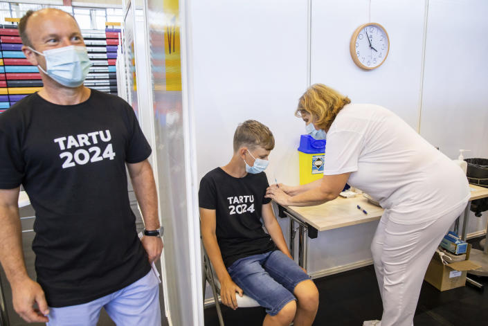 A medical worker, right, administers a shot of a coronavirus vaccine to Joonas Leis , 12 years old boy, center, as his father Kuldar stands near at a vaccination center inside a sports hall in Estonia's second largest city, Tartu, 164 km. south-east from Tallinn, Estonia, Thursday, July 29, 2021. Estonia's second largest city Tartu is making rapid progress in vaccinating children aged 12-17 ahead of the school year in September. Around half of the town's teenagers have already received their first vaccine, and local health officials are confident they will hit 70% in the coming 30 days. (AP Photo/Raul Mee)