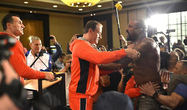 Former heavyweight world champion Shannon Briggs of the US, is pushed back by security after showing up at a press conference of boxer Wladimir Klitschko, left, of Ukraine during a press conference ahead of Klitschko's IBF, IBO, WBO and WBA heavyweight title bout against challenger Alex Leapai from Australia-Samoa in Duesseldorf, Germany, April 22, 2014. Briggs demanded a title fight against Klitschko in the US. (AP Photo/Martin Meissner)