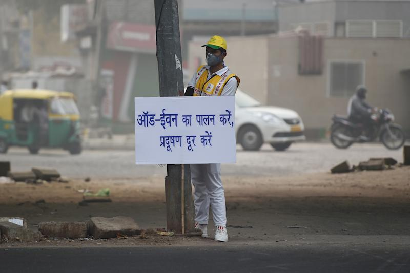 A volunteer from civil defence displays a placard to aware drivers on a street after the local government ordered half of the city's private cars to be taken off the road based on an odd-even registration plate system to help reduce air pollution, in New Delhi on Nov. 4, 2019. (Photo: Money Sharma/AFP via Getty Images)