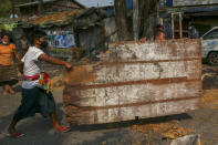 Anti-coup protesters carry debris to build makeshift barricades to prevent security forces from advancing in Mandalay, Myanmar, Tuesday, March 2, 2021. Demonstrators in Myanmar took to the streets again on Tuesday to protest last month's seizure of power by the military, as foreign ministers from Southeast Asian countries met to discuss the political crisis. Police in Yangon, Myanmar's biggest city, used tear gas and rubber bullets against the protesters.(AP Photo)