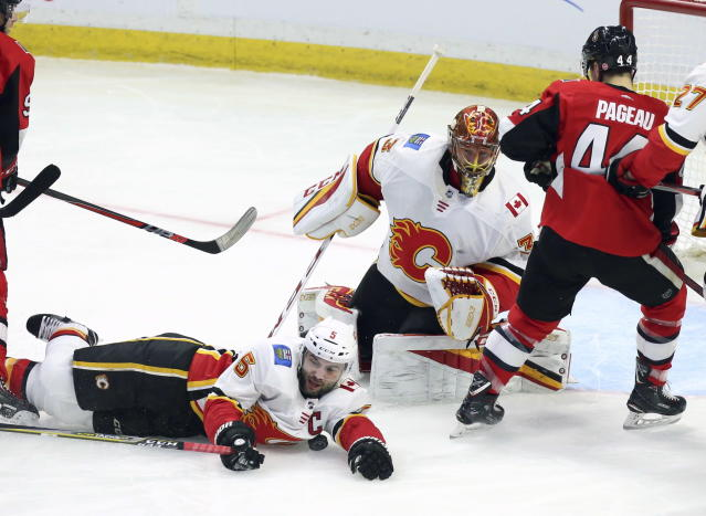 Calgary Flames defenseman Mark Giordano (5) smothers the puck as goaltender David Rittich (33) and Ottawa Senators center Jean-Gabriel Pageau (44) look on during the second period of an NHL hockey game in Ottawa, Friday, March 9 2018. (Fred Chartrand/The Canadian Press via AP)
