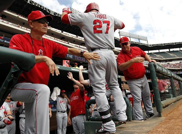 Los Angeles Angels bench coach Rob Picciolo, left, and manager Mike Scioscia, right, congratulate Mike Trout (27) as he enters the dugout following his solo home run in the first inning of a baseball game against the Texas Rangers, Sunday, Sept. 29, 2013, in Arlington, Texas. The shot came off a pitch from Rangers starter Yu Darvish. (AP Photo/Tony Gutierrez)