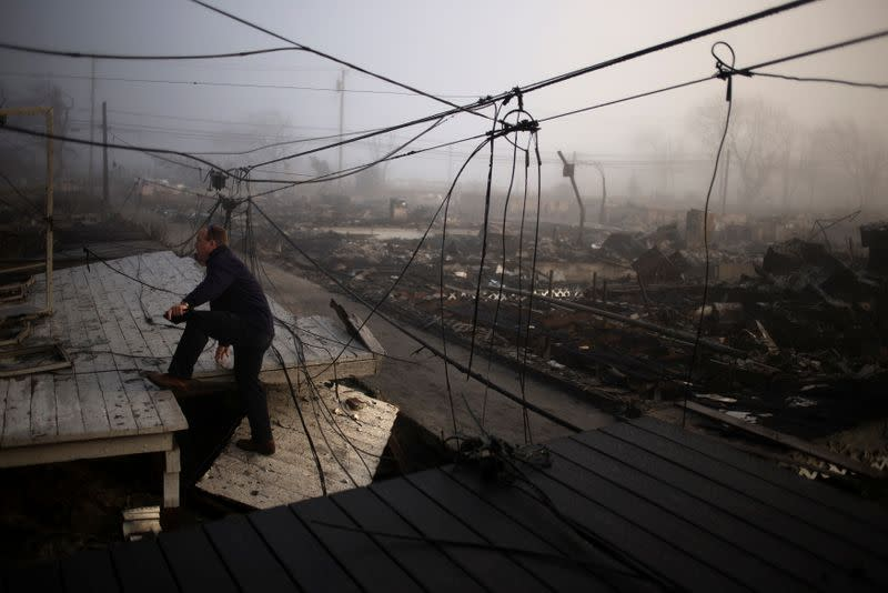 FILE PHOTO: An insurance claims adjuster climbs the entrance to a house in the Breezy Point neighborhood which was left devastated by Hurricane Sandy in the New York borough of Queens