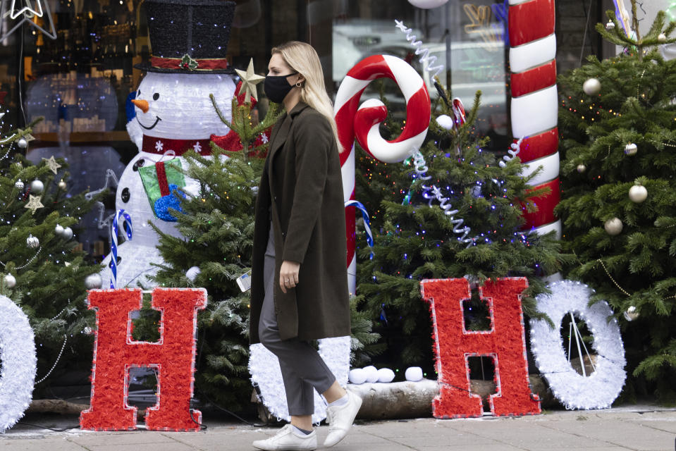 LONDON, ENGLAND - NOVEMBER 23: A woman wearing a facemask walks past Christmas decorations outside a wine shop in Mayfair on November 23, 2020 in London, England. UK Prime Minister, Boris Johnson, will announce plans for new coronavirus restrictions to the House of Commons once the current lockdown comes to an end on December 2nd. (Photo by Dan Kitwood/Getty Images)