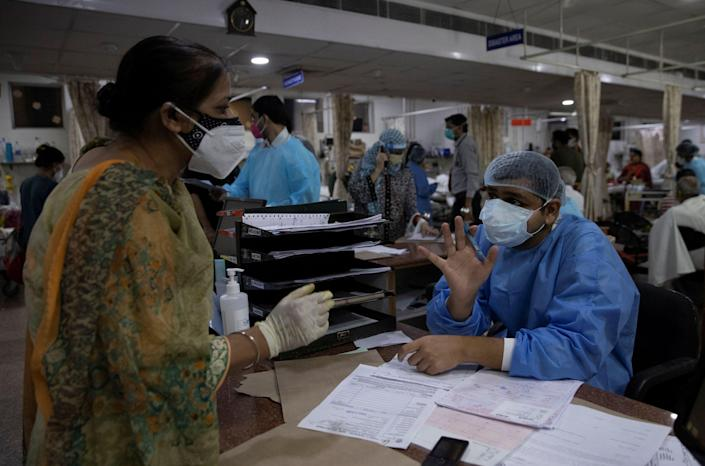 <p>Rohan Aggarwal, 26, a resident doctor treating patients suffering from coronavirus, talks to the relative of a Covid-19 patient about the unavailability of hopsital beds during his 27-hour shift at the Holy Family Hospital in New Delhi, India</p> (Reuters)
