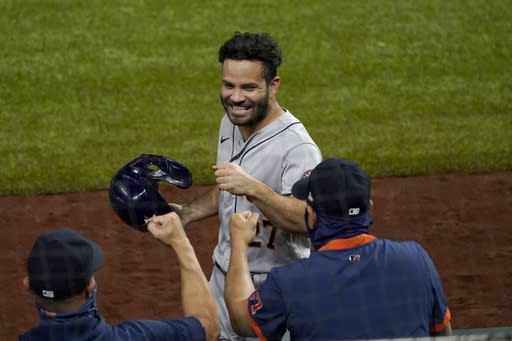 Houston Astros' Jose Altuve celebrates with staff in the dugout after scoring on a Yuli Gurriel single in the eighth inning of a baseball game against the Texas Rangers in Arlington, Texas, Friday, Sept. 25, 2020. (AP Photo/Tony Gutierrez)