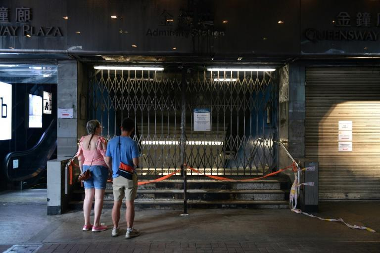 Tourists look at the closed and vandalised Admiralty metro station -- increased vandalism in Hong Kong has shocked a city known for its stability (AFP Photo/Nicolas ASFOURI)