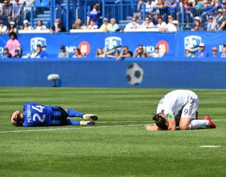 May 21, 2018; Montreal, Quebec, CAN; Montreal Impact defender Michael Petrasso (24) and Los Angeles Galaxy forward Zlatan Ibrahimovic (9) react on the turf during the first half at Stade Saputo. Mandatory Credit: Eric Bolte-USA TODAY Sports